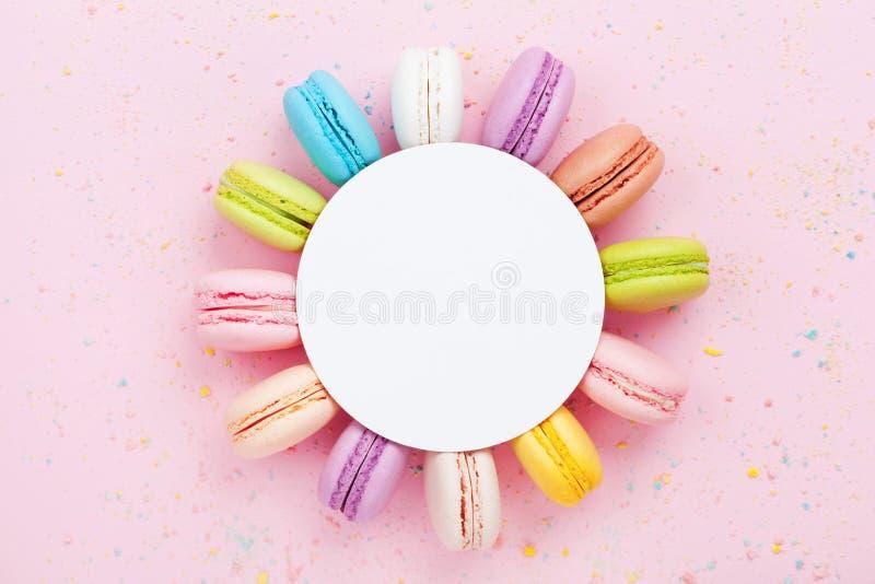 与五颜六色的macaron的在桃红色淡色背景顶视图的大模型或蛋白杏仁饼干 平的位置构成 图库摄影