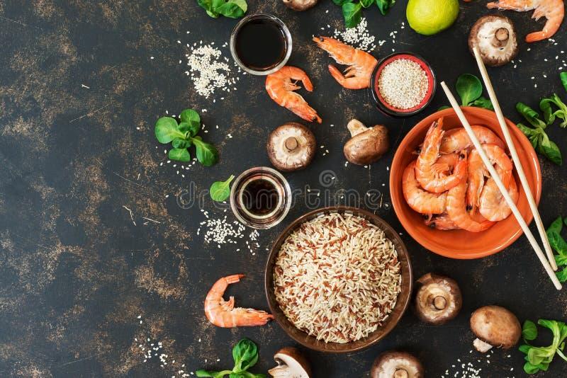 与亚洲烹调糙米、虾和蘑菇成份的背景  顶视图,拷贝空间 免版税库存图片