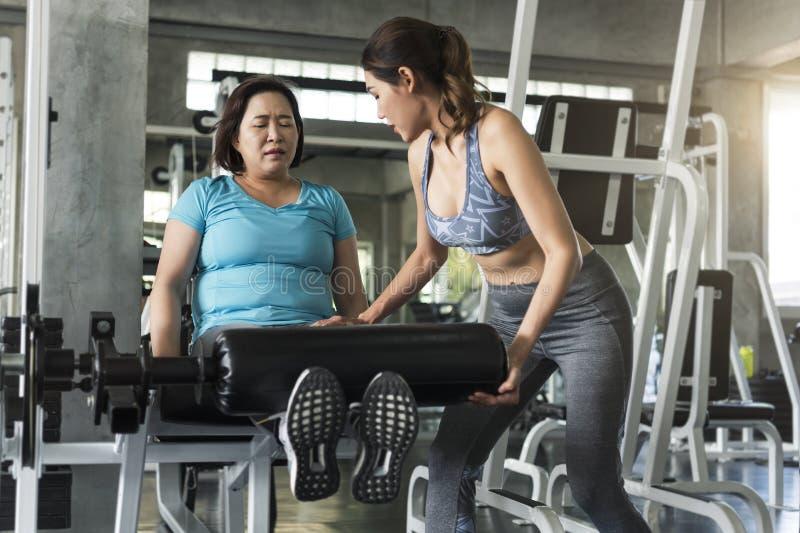 与亚裔资深妇女举的杠铃的教练员在健身房 健康生活方式和锻炼概念 库存图片