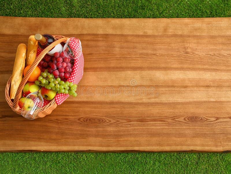 与产品的野餐在木表面室外,顶视图的篮子和酒 库存照片