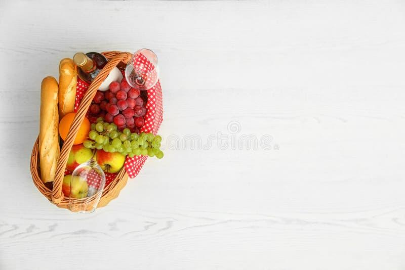 与产品的野餐在白色木桌,顶视图上的篮子和酒 库存图片