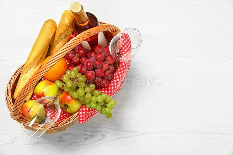 与产品的野餐在白色木桌,顶视图上的篮子和酒 免版税库存照片