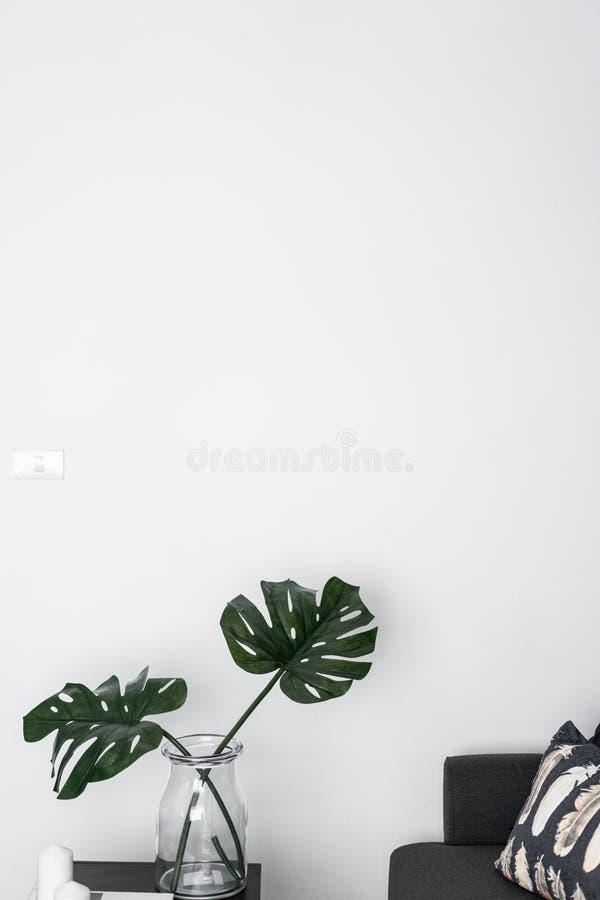 与人为植物的沙发角落有空的白色被绘的墙壁/空间的玻璃花瓶的做广告/内部行销的 库存图片