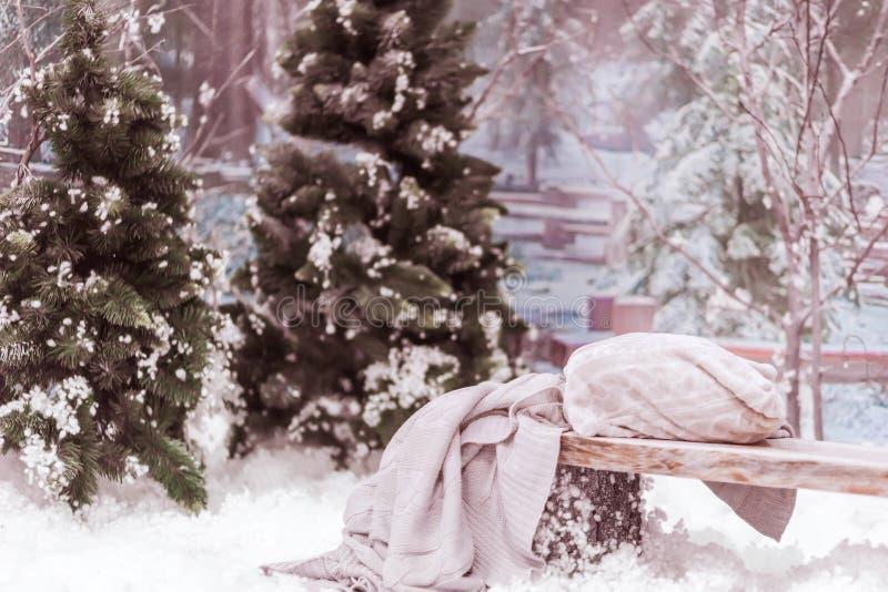 与人为雪、圣诞树和一条长凳的新年的装饰与枕头 库存图片