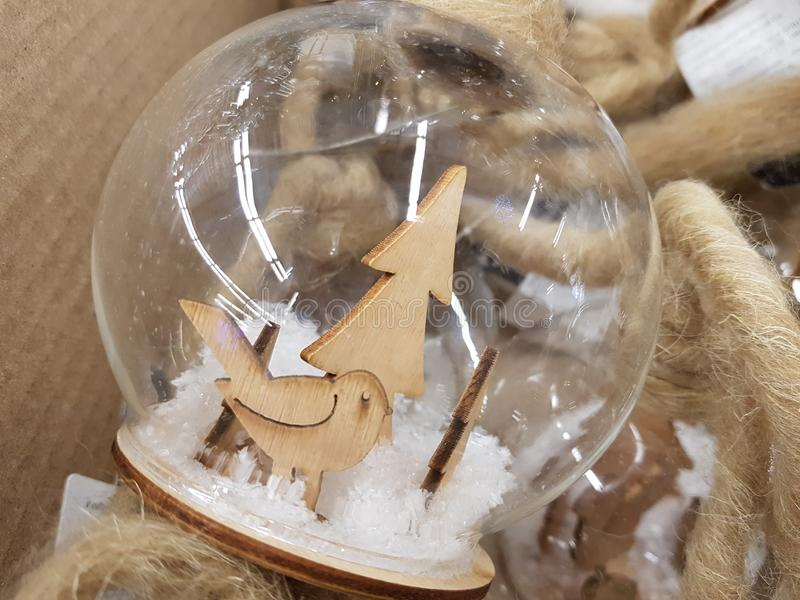 与人为雪和鸟和冷杉木的木图的透明玻璃球形 库存图片