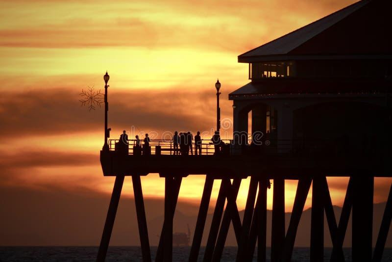 与人和亨廷顿海滩码头剪影的橙色日落天空  免版税库存照片
