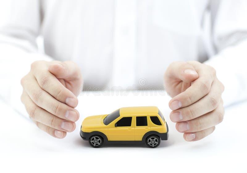 与人工包括的黄色汽车玩具的汽车保险概念 库存图片