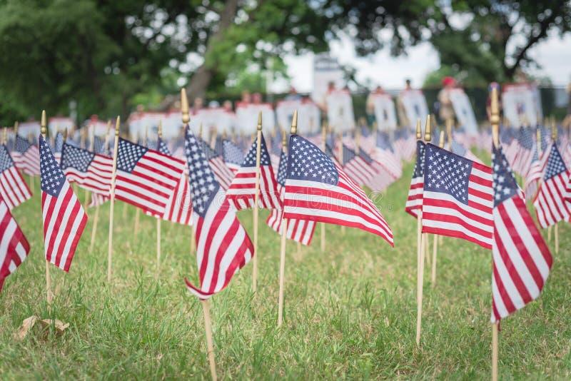 与人模糊的行的草坪美国国旗运载横幅游行的下落的战士 免版税库存图片