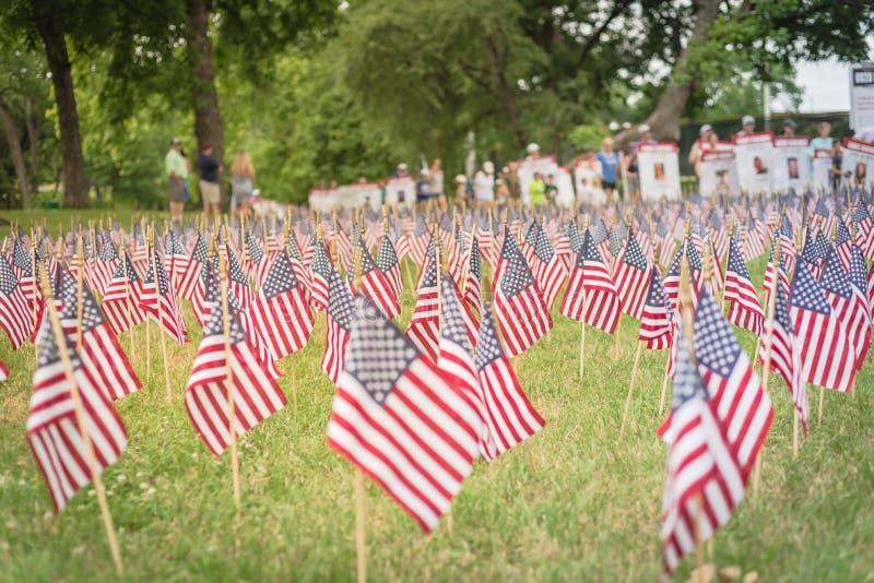 与人模糊的行的草坪美国国旗运载横幅游行的下落的战士 图库摄影