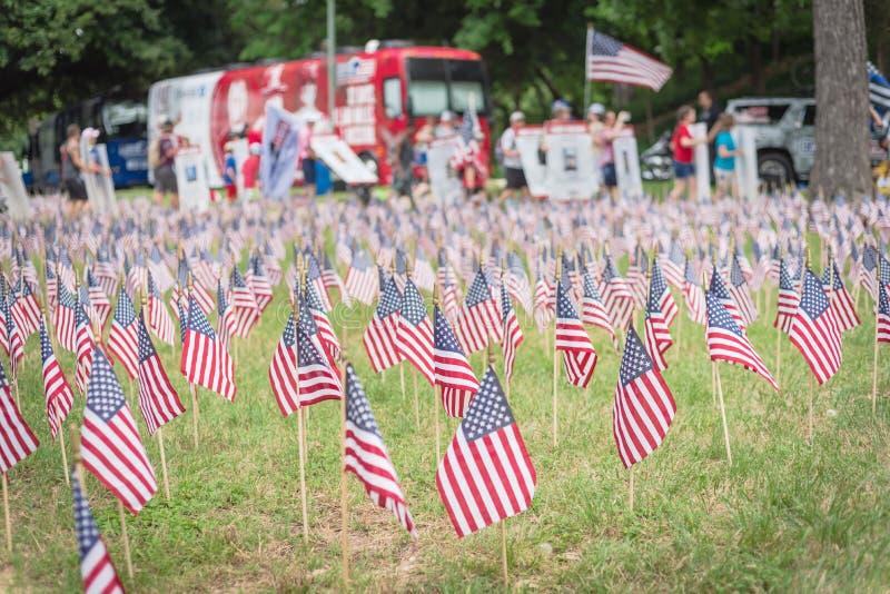 与人模糊的行的草坪美国国旗运载横幅游行的下落的战士 库存图片