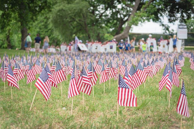 与人模糊的行的草坪美国国旗运载横幅游行的下落的战士 免版税库存照片