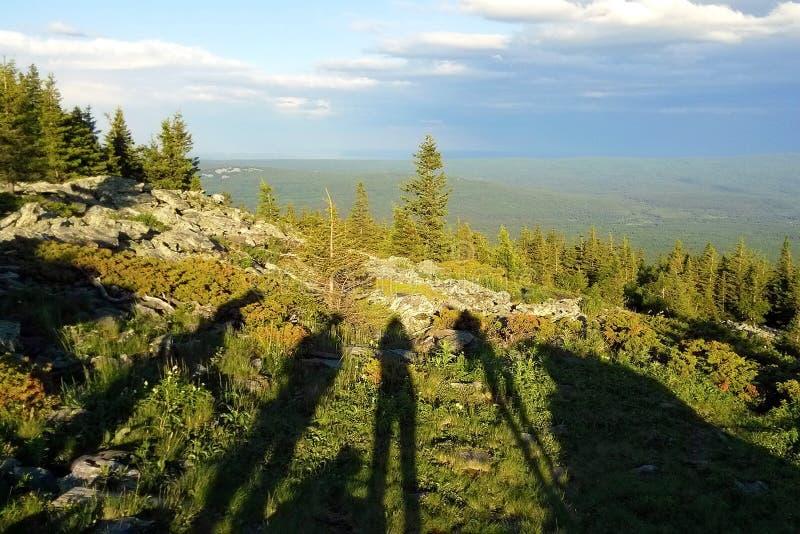 与人民的阴影在山、森林和多云天空的看法的 免版税库存照片
