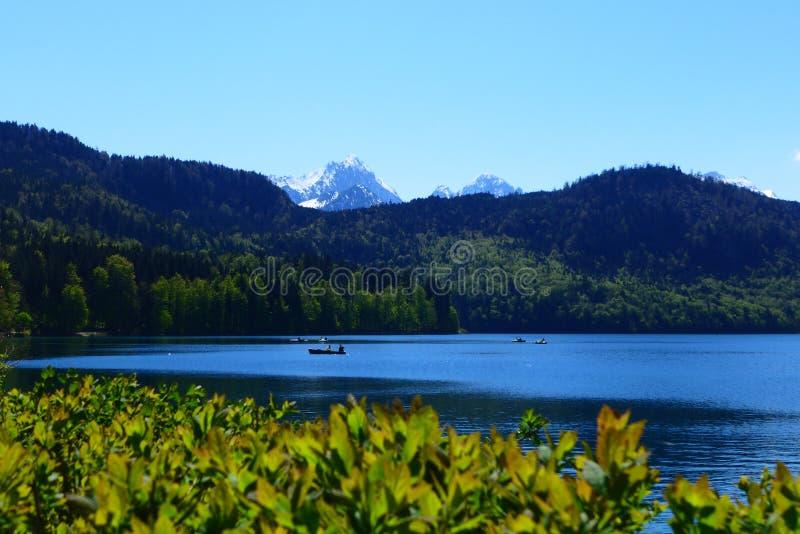 与人的高山风景小船的 免版税库存照片