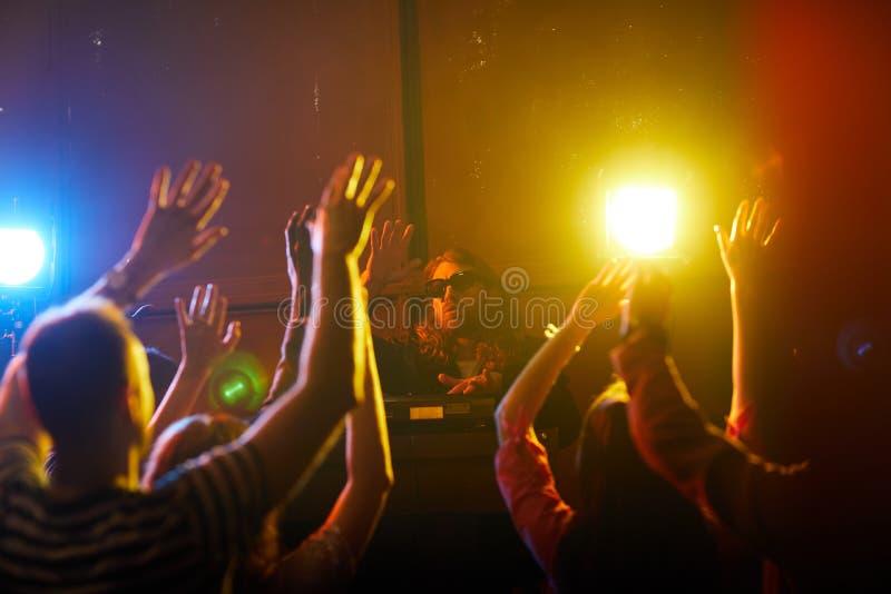 与人群一起的年轻DJ挥动的手 图库摄影