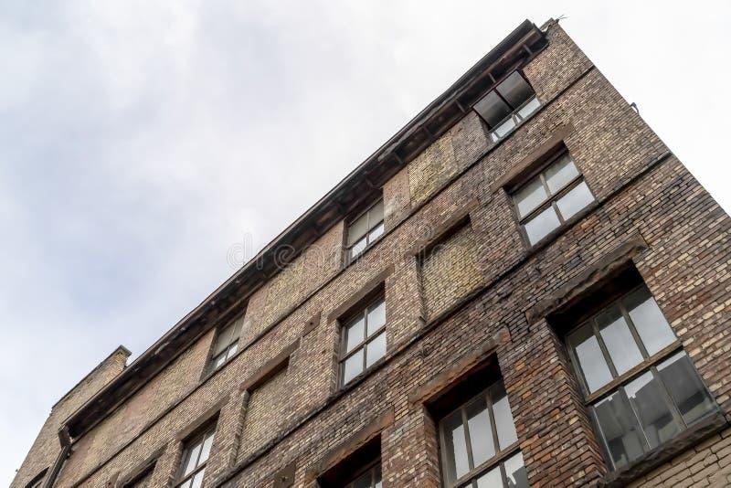 与从地面观看的砖外墙的老大厦反对多云天空 免版税图库摄影