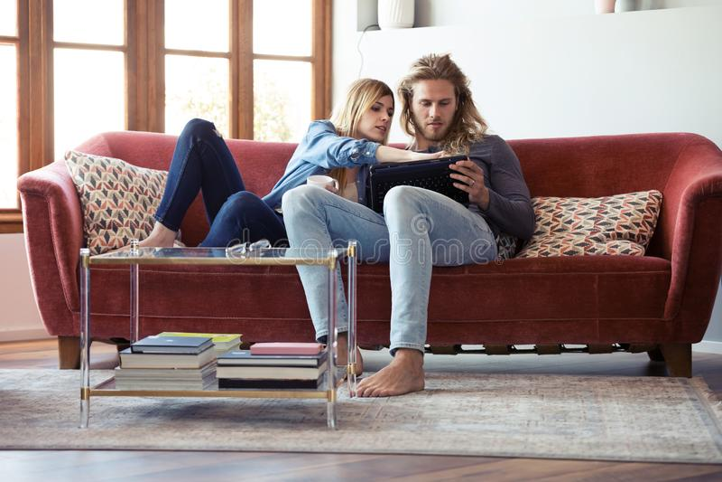 与他们的可爱的年轻夫妇图画数字片剂,当在家时坐沙发 免版税库存图片