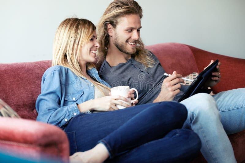 与他们的可爱的年轻夫妇图画数字片剂,当在家时坐沙发 库存图片