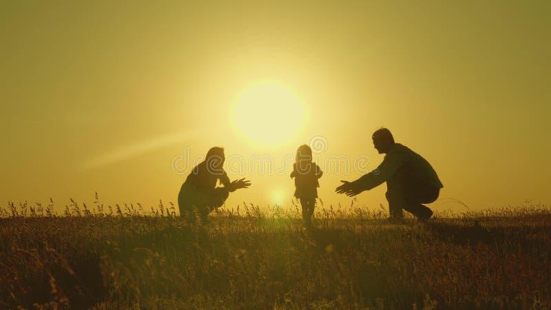 与他们的女儿的母亲和爸爸戏剧在阳光下 愉快的婴孩从爸爸去妈妈 在领域的年轻家庭与a 免版税图库摄影