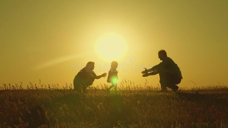 与他们的女儿的母亲和爸爸戏剧在阳光下 愉快的婴孩从爸爸去妈妈 在领域的年轻家庭与a 库存图片