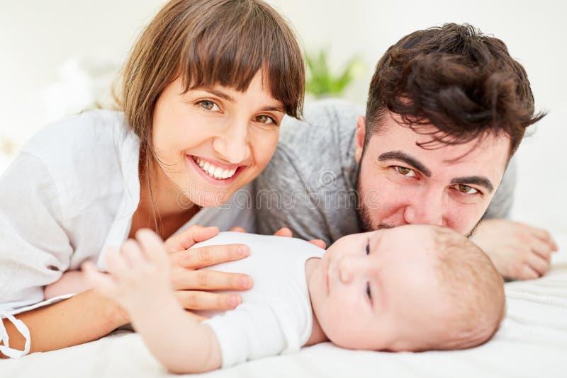 与他们的婴孩一起的愉快的父母 免版税库存照片