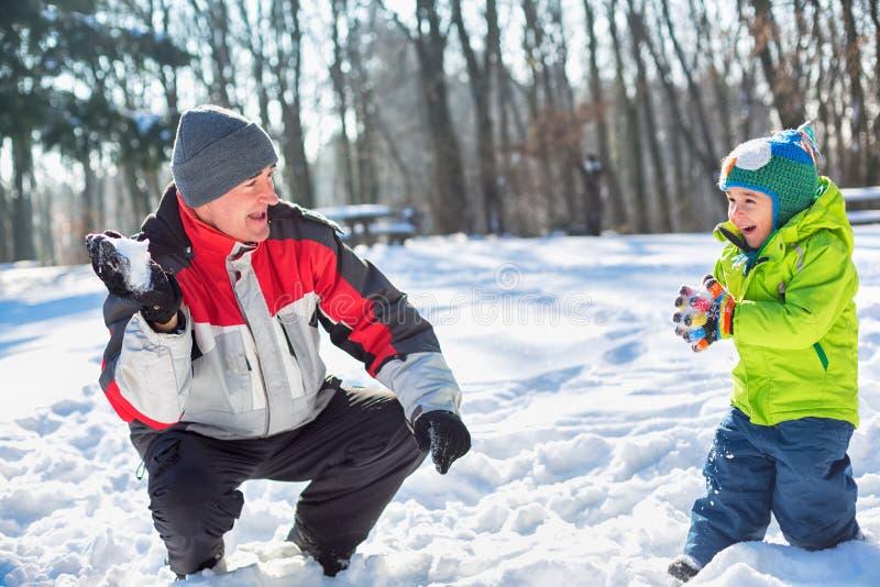 与他的孙子的祖父投掷的雪球 图库摄影