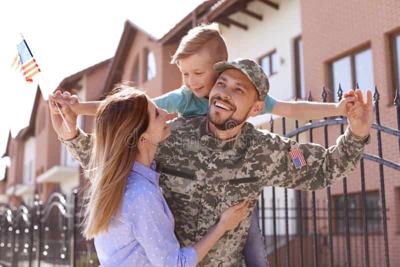 与他的家庭团聚的男性战士户外 兵役 免版税库存图片