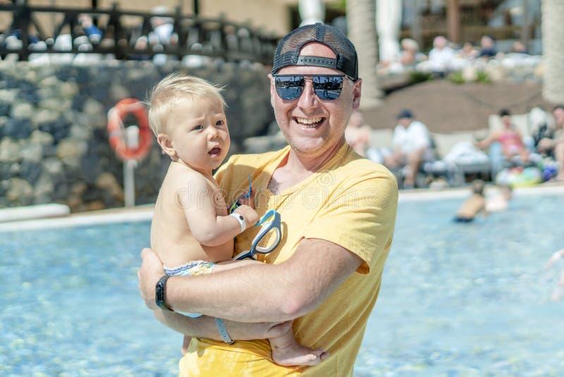 与他的小儿子的愉快的父亲消费时间由在手段的水池 免版税库存图片