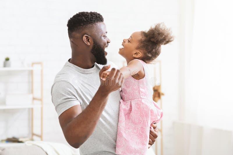 与他的小女儿的快乐的黑人跳舞 库存照片