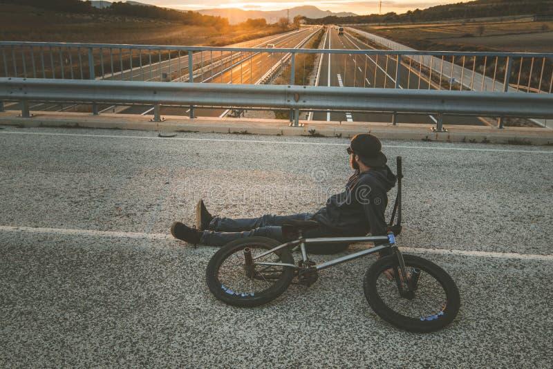 与他的bmx自行车的BMX车手在街道上 在bmx的人骑马 库存照片