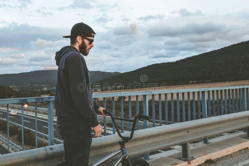 与他的bmx自行车的BMX车手在街道上 在bmx的人骑马 免版税库存图片