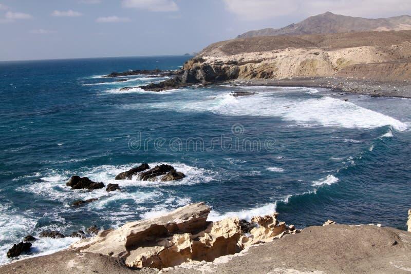 与令人惊讶的峭壁和蓝色风大浪急的海面的惊人自然观点费埃特文图拉岛,加那利群岛,西班牙西北海岸的  库存图片