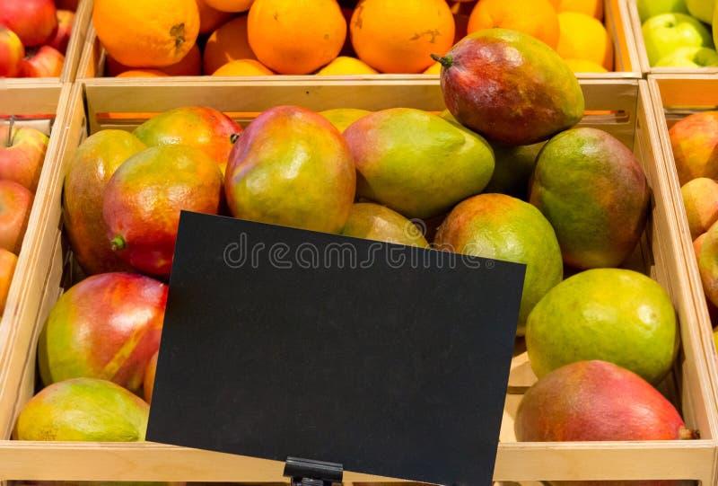与价牌的芒果在桶 图库摄影