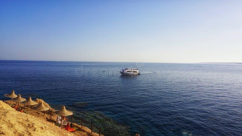 与伞和船,Sharm El谢赫,埃及的美丽的红海海滩 图库摄影