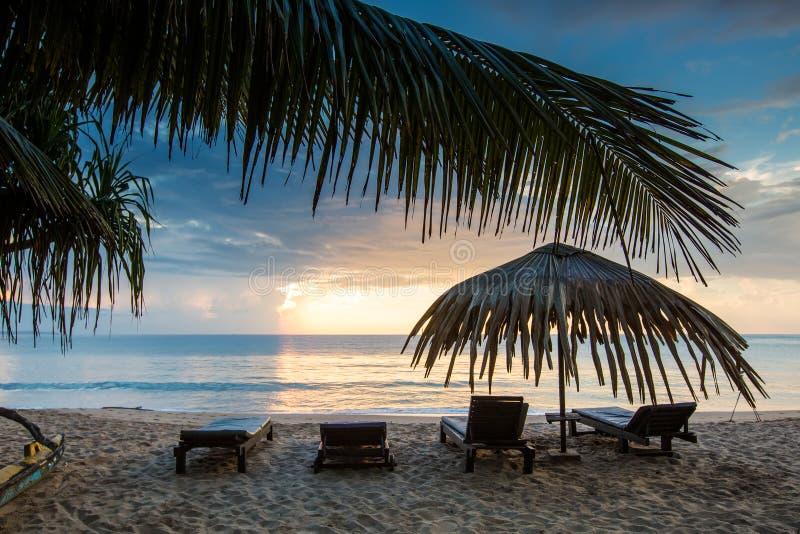与伞在海滩,日落的太阳懒人 库存图片