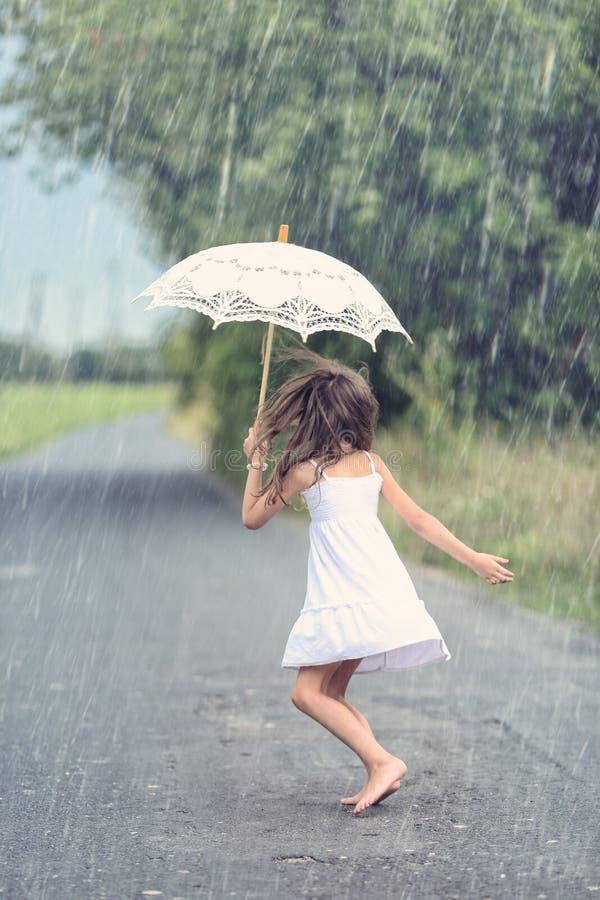 与伞的快乐的女孩舞蹈在雨中 免版税库存照片