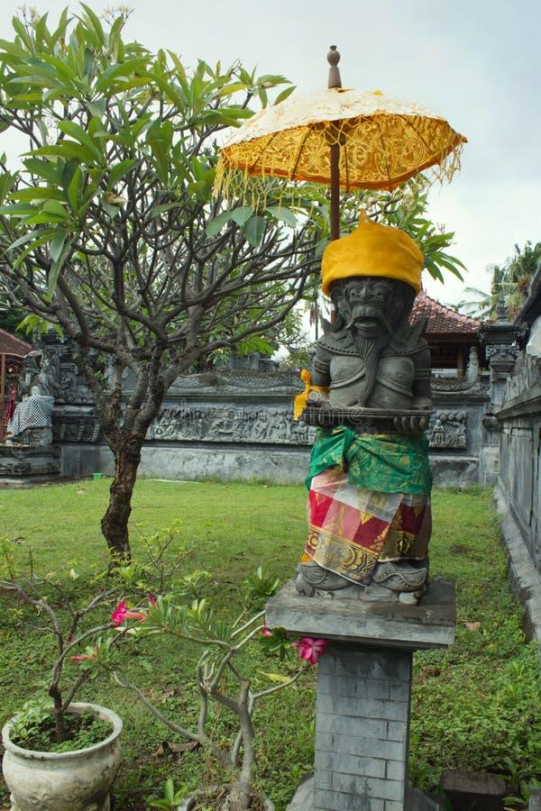 与伞的监护人雕象在寺庙在Lovina巴厘岛,印度尼西亚 免版税库存照片