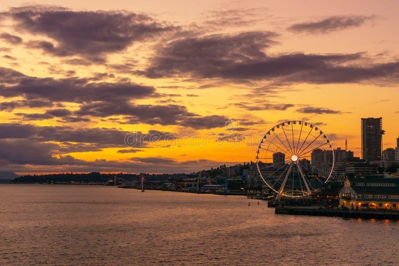 与伟大或弗累斯大转轮的充满活力和五颜六色的西雅图地平线waterfont在日落或黄昏从埃利奥特海湾,华盛顿州 免版税库存照片