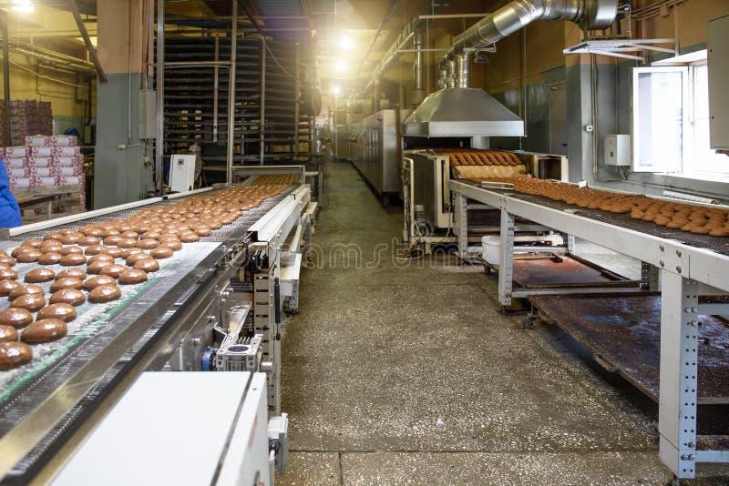 与传动机线或传送带的工业烘烤的食物工厂内部 面包店车间、蛋糕和曲奇饼生产过程 免版税库存图片
