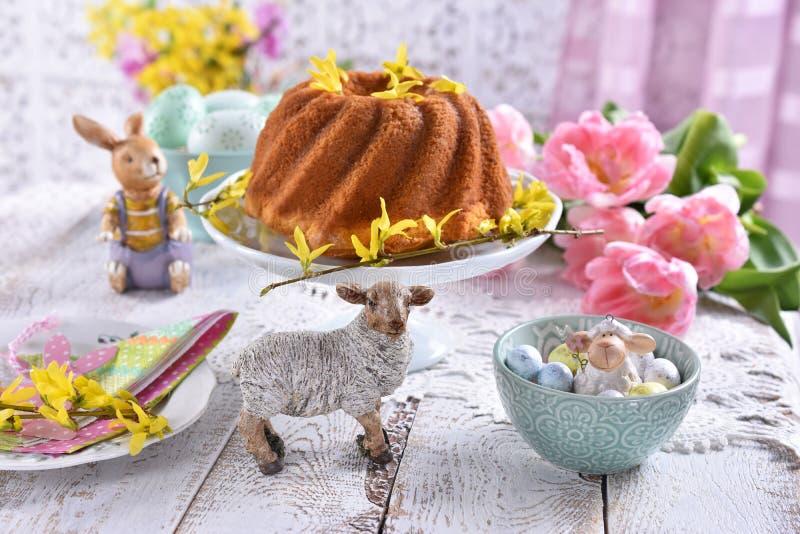 与传统圆环蛋糕和郁金香的复活节欢乐桌 免版税库存照片
