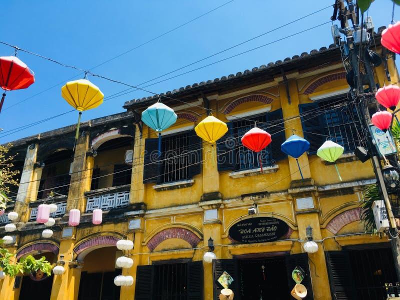与传统灯的芥末黄色大厦在会安市古镇,越南 免版税库存照片