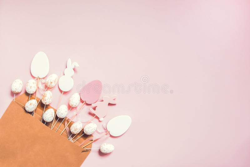 与传统装饰的复活节构成 在工艺纸信封的装饰五颜六色的蛋和兔子木形象在浅粉红色 库存照片