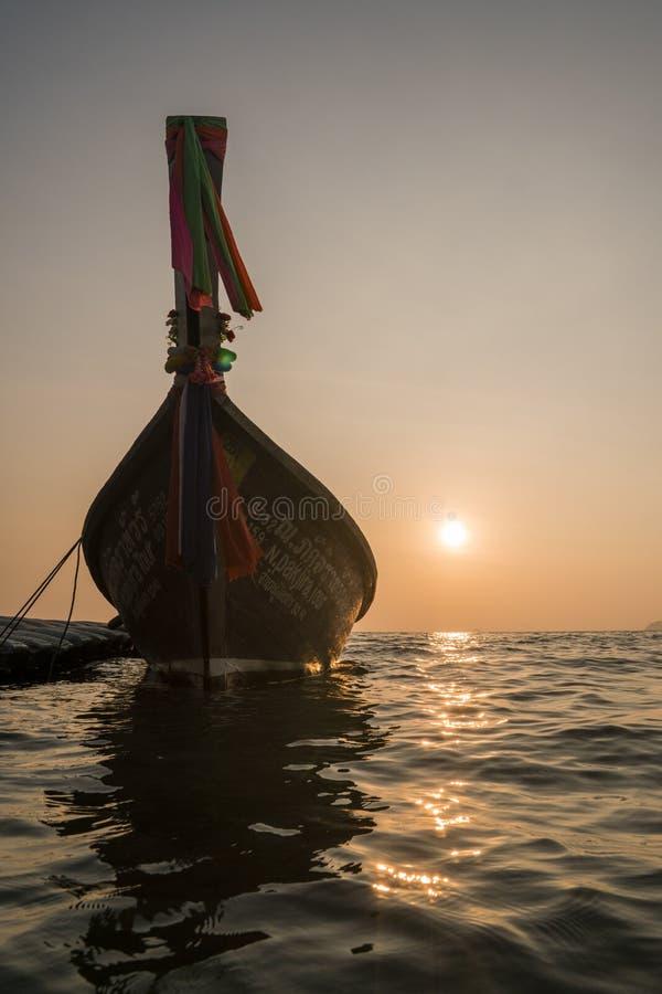 与传统Longtail小船剪影的日落在海 泰国 图库摄影