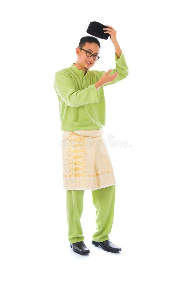 与传统马来的服装的亚洲回教男性在微笑的acti 免版税图库摄影