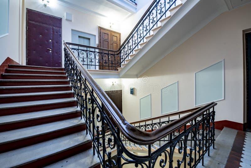 与伪造的栏杆的楼梯在老楼梯间的栏杆 库存照片