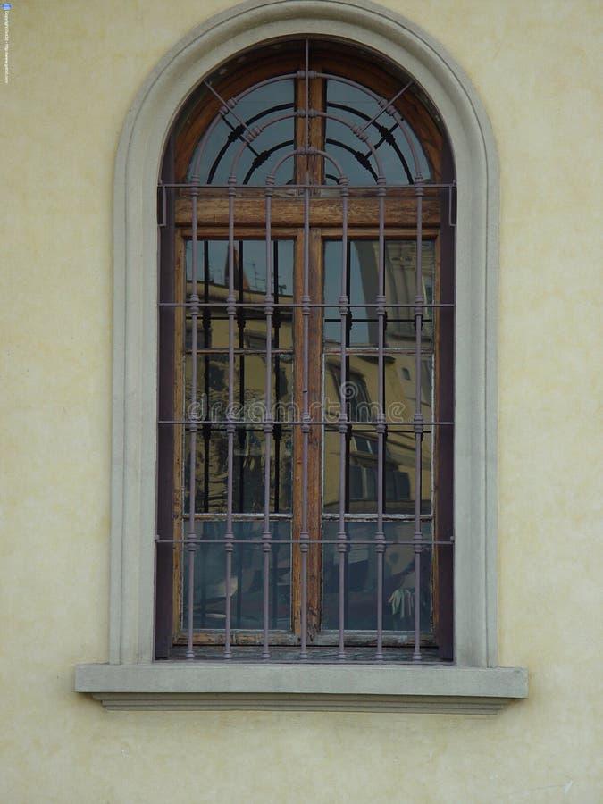 与伪造的钢滤栅和造型的木被成拱形的窗口 库存照片