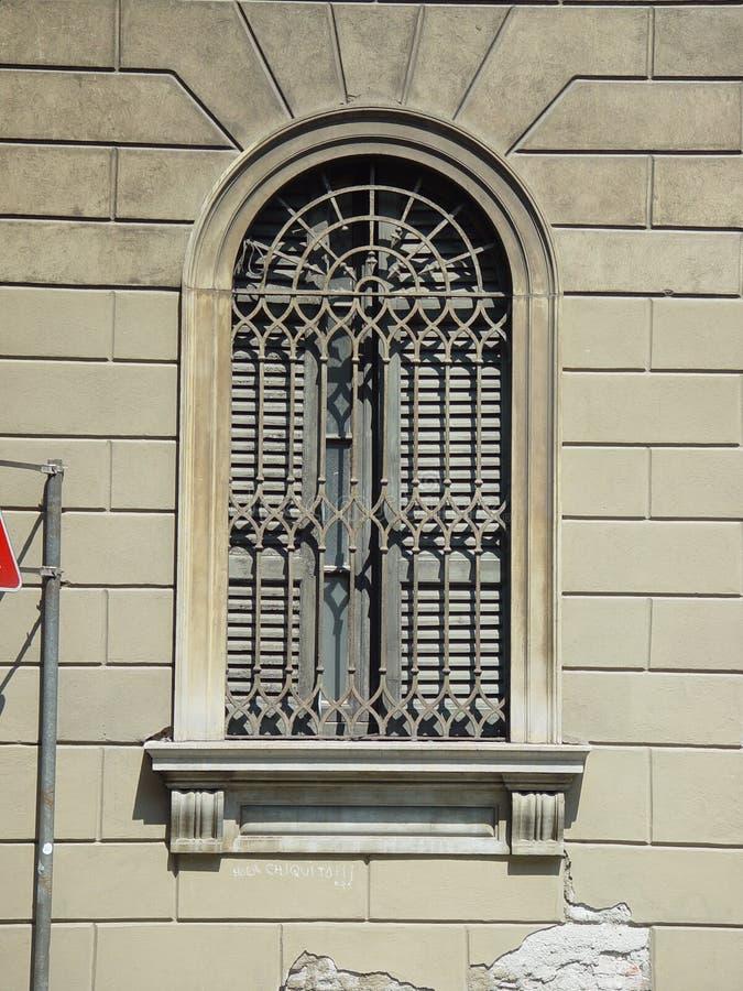 与伪造的钢滤栅的典雅的被成拱形的窗口 免版税库存照片