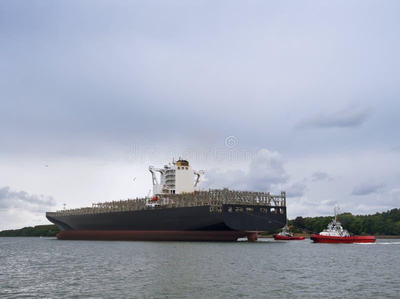 与伴游的货船,空的集装箱船 免版税图库摄影