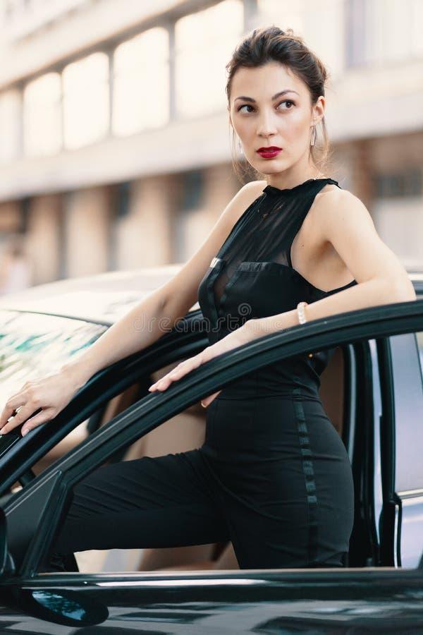 与似猫的神色的肉欲的危险妇女身分在准备好的汽车的门赢得世界 免版税库存图片