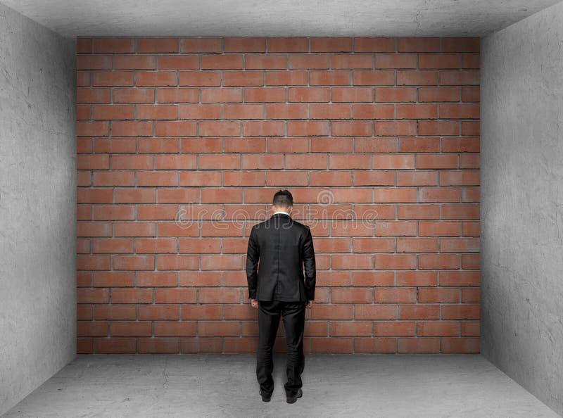 与低下的头的商人站立一个砖墙的前面在内部的 免版税图库摄影