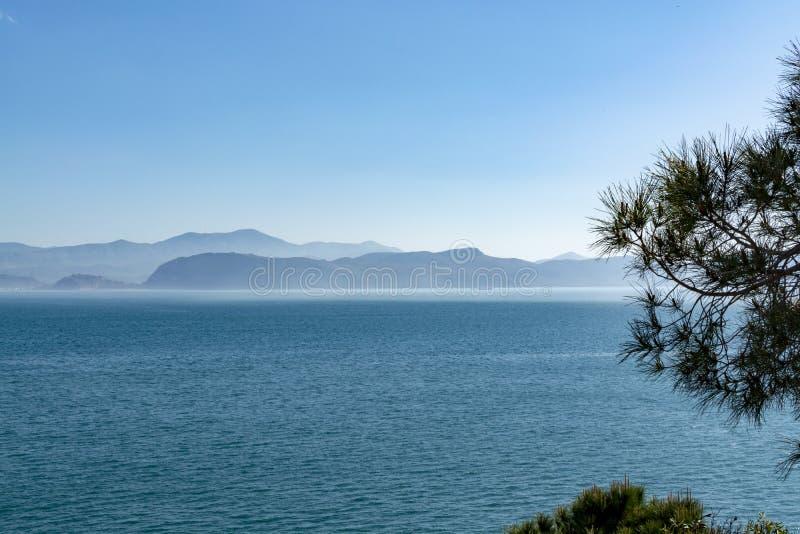 与低雾云彩的海景在海水在与太阳光的清早 免版税库存图片